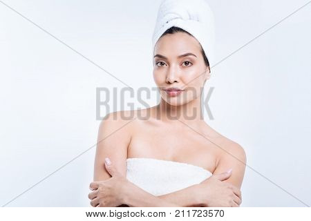 After hot shower. Beautiful young woman with a swarthy complexion having her hair wrapped in a towel turban while wearing only a towel, having taken a shower