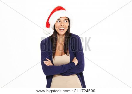 Portrait of a smiling cheerful woman in christmas hat looking away with arms folded isolated over white background