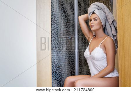Woman With Towel On Her Head Sitting On The Toilet
