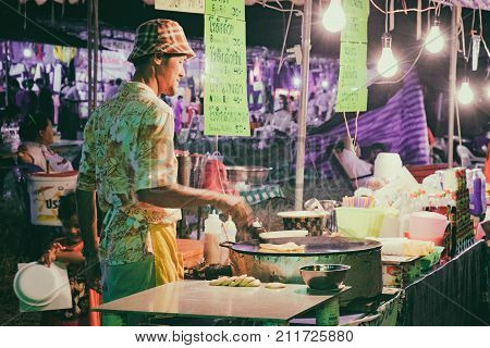 Khao Lak, Thailand - December 27, 2015: Thai Man cooking Roti Mataba for sale traveller at street night market in Khao Lak, Thailand. Street cooking is a tradition and ubiquitous in Thailand.