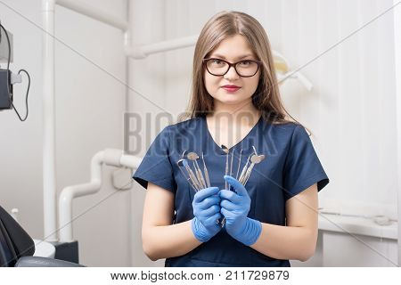 Portrait Of Young Female Attractive Dentist Holding Dental Tools - Mirrors And Probes At The Morden