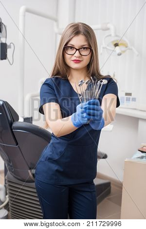 Portrait Of Attractive Female Dentist Holding Dental Tools At The Morden Dental Office. Doctor Weari