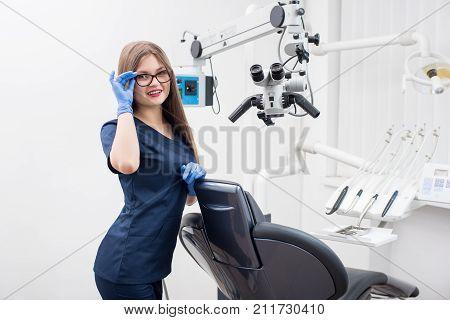 Portrait Of Happy Female Assistant At The Morden Dental Office. Doctor Wearing Glasses, Blue Uniform
