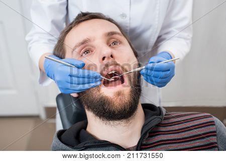 Close Up Of Bearded Man Having Dental Check Up In Dental Office. Dentist Examining A Patient's Teeth