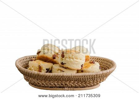 Homemade raisin scones in basket with white isolated background and clipping paths. Scones is traditional English pastry so delicious for afternoon tea or coffee break. Homemade bakery concept. Raisin scones isolated white concept for web design.