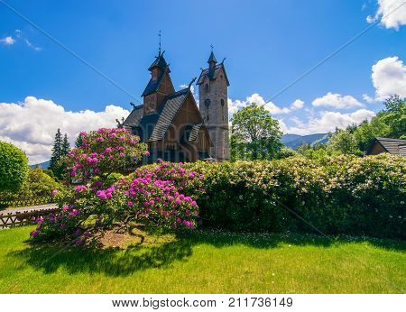 Vang medieval norwegian wooden church with blooming rhododendron bush on foreground in Karpacz Lower Silesia Poland Giant Mountains