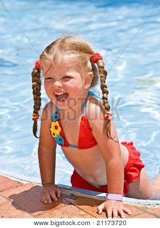 Child girl in red bikini near blue swimming pool. Summer.