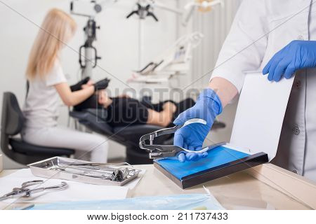 Close-up View Of Assistant's Hands With Blue Gloves Working With Dental Tools, On The Blurred Backgr