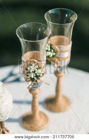 Two wedding champagne glasses decorated with twine and flowers standing on table.