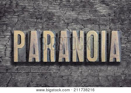 paranoia word made from vintage letterpress type on burned wood background
