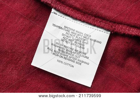 Washing instructions and fabric composition clothes label on red cotton