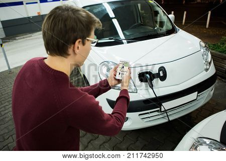 Man with phone on a background of electric cars charging point. E-car sharing concept