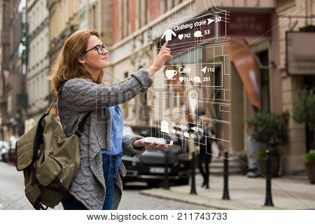 Augmented reality in marketing. Woman traveler with phone. Navigation on the projection of the display poster