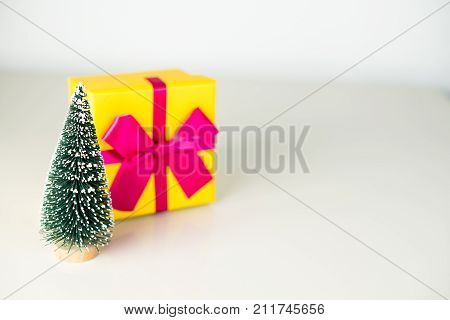 Sigh symbol Christmas tree and gift on light background. Empty copy space for inscription. Idea of merry new year 2018 holiday.