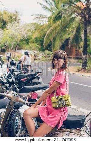 Closeup attractive beautiful woman with snakeskin python handbag posing outdoors.