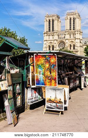 Paris France - June 23 2017: Vintage books and paintings in open bookmarket on embankment of River Seine near Notre Dame de Paris Cathedral. The bookmarket is there since the 16th century.