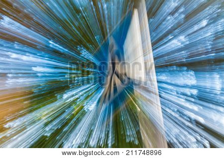 Abstract background of road sign on the background of tree crown and sky in motion blur