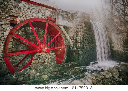 working water mill with a red wheel. old grist mill