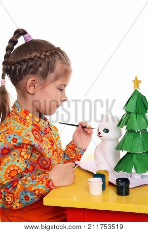 A girl paints the figure of a white cat out of papier-mache. Preparing for the New Year