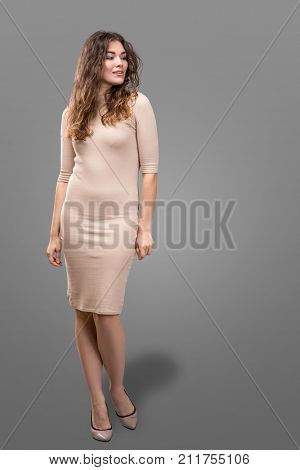 Fashion style woman perfect body shape brunette hair wear light beige dress suit elegance casual beautiful model secretary air hostess diplomatic protocol office uniform stewardess business lady isolated over grey background.