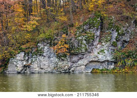 Rocky Cliff Above The River In Autumn Forest