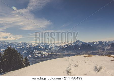 Scenery of footprint in snow on cliff with rock mountain range in winter background under blue clear sky and wonderful cloud shape, Landscape of Swiss Alps hill in Switzerland behind snowy ground stamp by animal spoor