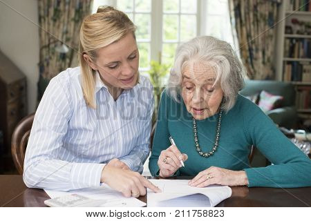 Mature Woman Helping Senior Neighbor With Paperwork