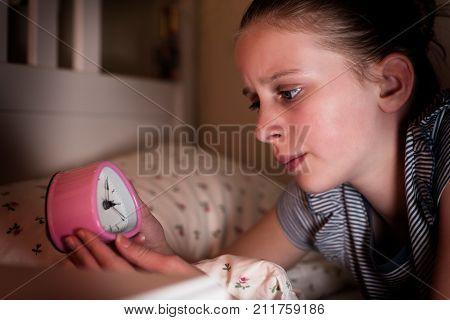 Anxious Girl Unable To Sleep At Night Looking At Clock