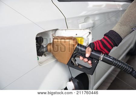 Men hold Fuel nozzle to add fuel in car at filling station