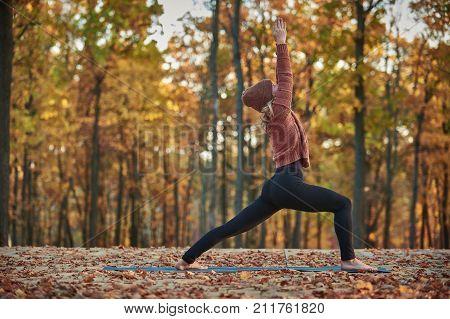 Beautiful young woman practices yoga asana Virabhadrasana 1 - warrior pose on the wooden deck in the autumn park
