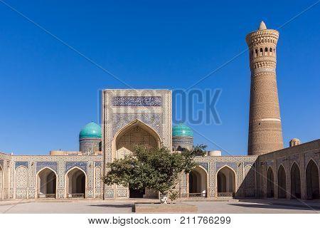 Courtyard at Po-i-Kalyan, with the madrasa and minaret - Bukhara, Uzbekistan. The complex include Kalyan four-iwan mosque and Kalyan minaret.