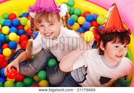 Children in party hat with ball.