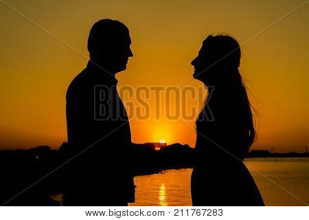 Sunset Love Story In The Sea. Young Couple Make The Sign Of Hands Hearts In The Air Before Sunrise.