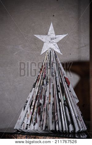 paper christmas tree in living room interier . Home made christmas decoration, paper tree from newspaper or magazine.Old style christmas tree
