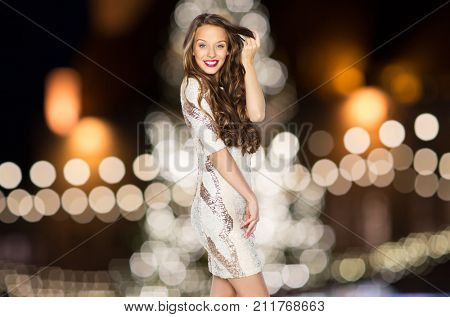 holidays, hairstyle and people concept - happy young woman or teen girl in fancy dress with sequins touching long wavy hair over christmas tree lights background