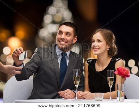 people, service and holidays concept - smiling couple paying for dinner with credit card at restaurant over christmas tree background