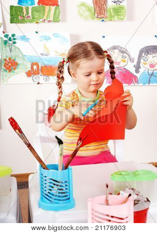 Child with scissors cut  paper  in playroom. Preschool.