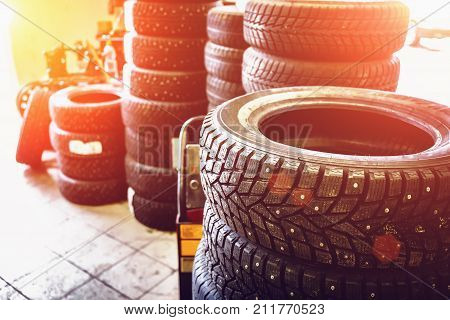 New winter tires in stacks inside automotive garage service - changing wheels or tires, sunlight effect, toned