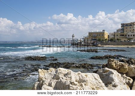Stones and blue ocean at the coast of Tyre with lighthouse at a sunny day with blue sky in Tyre, Sour, Lebanon