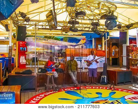 Philipsburg, Sint Maarten, Kingdom of the Netherlands - February 10, 2013: The musicians in a cafe at beach at Maho Bay. It is one of the world's premier planespotting destinations.
