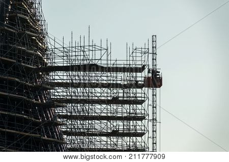 silhouette of scaffolding, working at building construction, profile sunset light structure of scaffolding with a crane lift