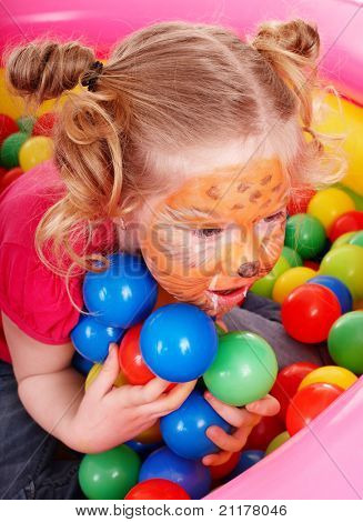 Little girl with paint on face  and group of  ball. Play room.