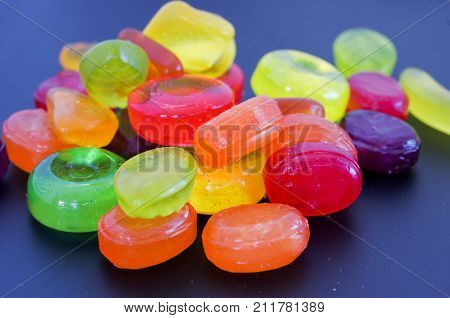 Many Multi-colored Sweets. Colored Sweets On A Dark Background.
