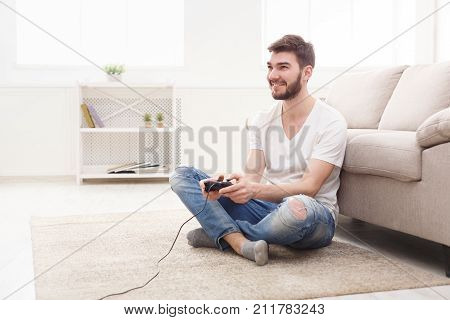 Young man playing video games at home. Happy guy sitting on floor with joystick in hands, copy space poster
