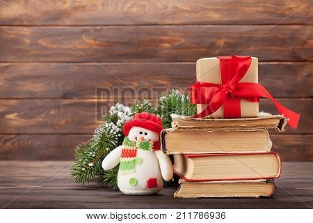 Christmas greeting card with xmas tree, books, gift box and snowman toy in front of wooden wall. With space for your greetings