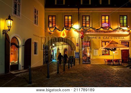 PRAGUE, CZECH REPUBLIC - DECEMBER 11, 2016: Narrow street and small restaurant decorated for Christmas in Old Town of Prague - famous tourist destination with more than 6 million visitors annually.
