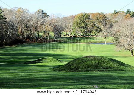 Humps and bumps on a lush, green well manicured golf hole on a sunny autumn day.