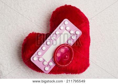 Medicine contraception love and birth control. Oral contraceptive pills condom on red heart shaped little pillow