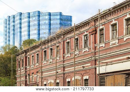 ROSTOV-ON-DON RUSSIA 07 OCTOBER 2017: Old dilapidated building on the street in the city of Rostov-on-Don against the background of a modern highrise building