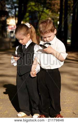 Children in business suit with mobile phone outdoors. Concept.